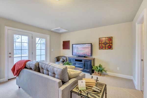 Veranda level entertainment room with comfy couch next to windowed door leading outside.