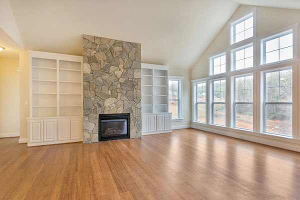 Craig Builders Pavilion great room featuring wood floors, a large bank of windows, and a cozy fireplace with stone.
