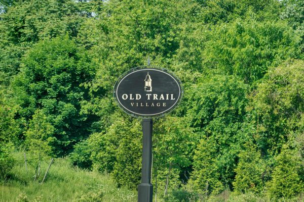 Old Trail Village sign against a background of foliage