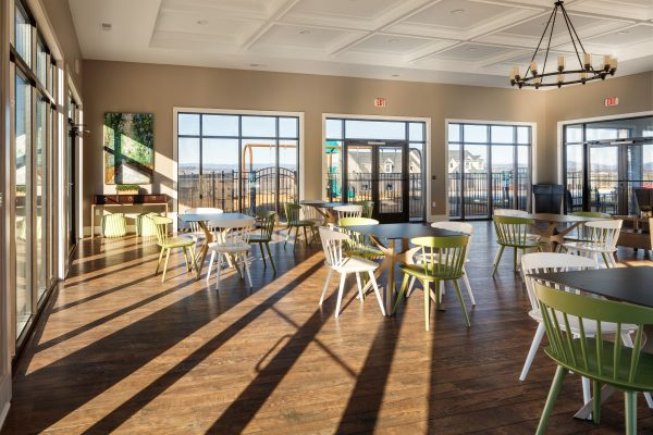 Cascadia clubhouse interior dining area with view of the playground through the windows.
