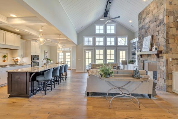 An open concept kitchen and great room with floor to ceiling windows. A comfortable living space centered around a stone fireplace is on the right, with a vaulted ceiling and ceiling fan above it. The kitchen is to the left with an island with upholstered high chairs.