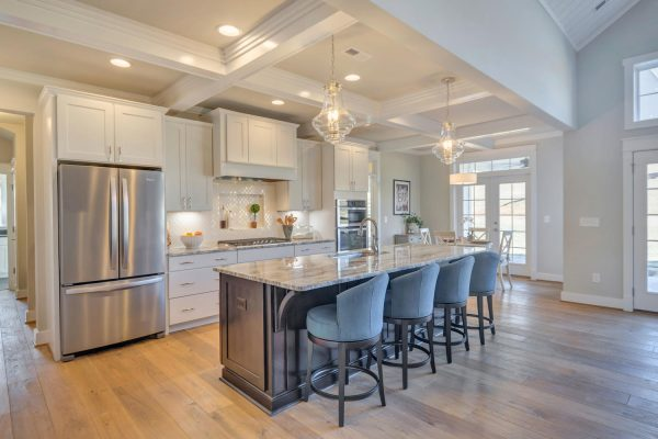 Craig Builders open kitchen in Oak Hill Farm. An elegant kitchen island with a built-in sink is situated beneath pendant lighting.