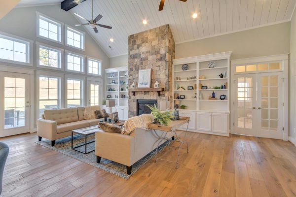 Craig Builders great room in Oak Hill Farm. A large bank of windows overlooks a small patio. Couches are arranged around a central stone fireplace.